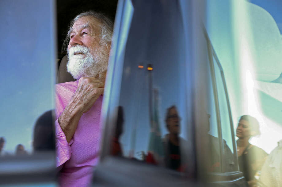 In this Thursday, Jan. 15, 2015 photo, Norberto Gonzalez Claudio, who completed a prison sentence for his role in a 1983 holdup in Connecticut carried out by Puerto Rican militants, looks out at supporters after arriving at the international airport in Carolina, Puerto Rico. The 69-year-old Puerto Rican arrived Thursday in the U.S. territory just hours after he was released from a prison in central Florida. Supporters greeted Gonzalez with raised fists in the air and waved Puerto Rican flags. (AP Photo/Gerardo Bello)