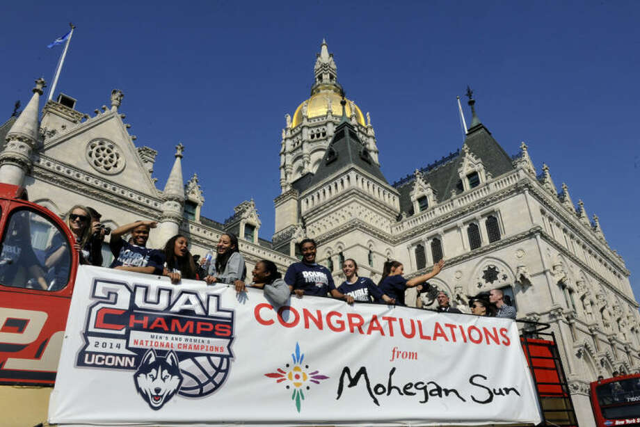 Members of Connecticut's women's basketball team wave to the crowd during a parade in Hartford, Conn., Sunday, April 13, 2014, while celebrating their recent NCAA national championship. (AP Photo/Fred Beckham)
