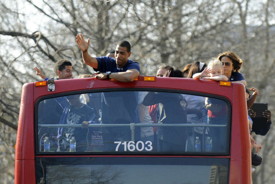 Connecticut men's basketball coach Kevin Ollie waves to a crowd during a parade in Hartford, Conn., on Sunday, April 13, 2014, celebrating UConn's wins in the NCAA men's and women's tournaments earlier this month. (AP Photo/Fred Beckham)
