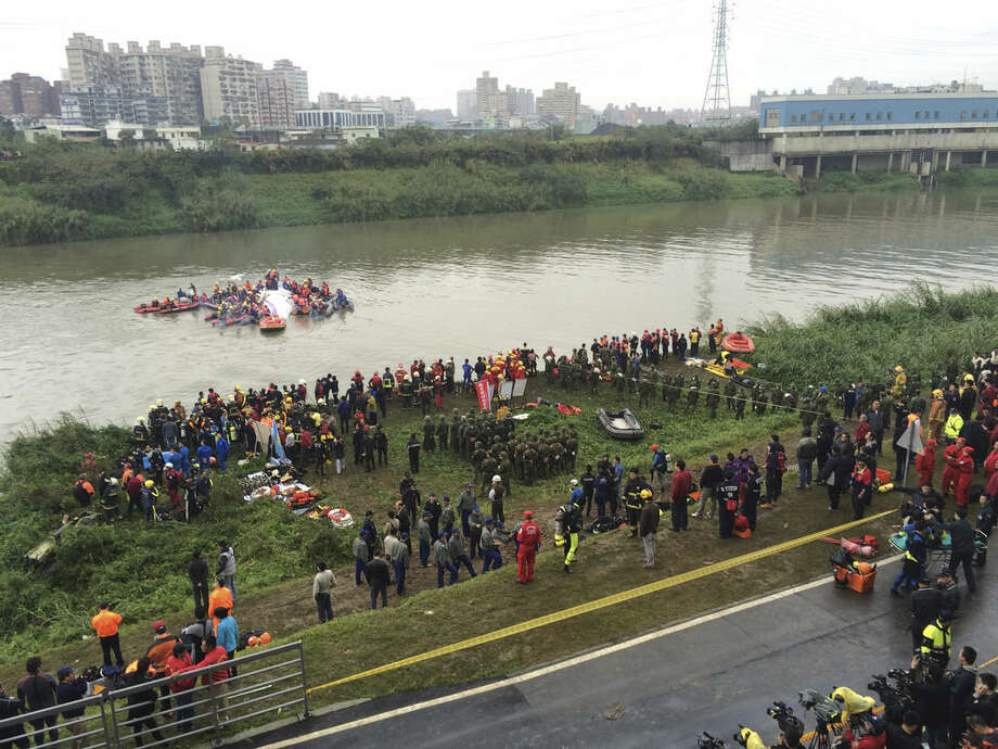 Emergency personnel work after a commercial plane after it crashed into a river in Taipei, Taiwan, Wednesday, Feb. 4, 2015. The Taiwanese commercial flight with 58 people aboard clipped a bridge shortly after takeoff and crashed into a river in the island's capital of Taipei on Wednesday morning. (AP Photo/Wally Santana)