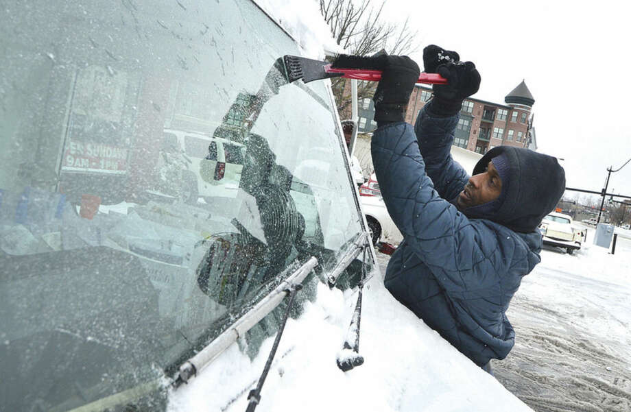 Hour Photo/Alex von Kleydorff Letter Carrier Terrell Johnson scrapes ice from the window of his postal vehicle while having chains placed on the tires at Curries Tires Monday morning