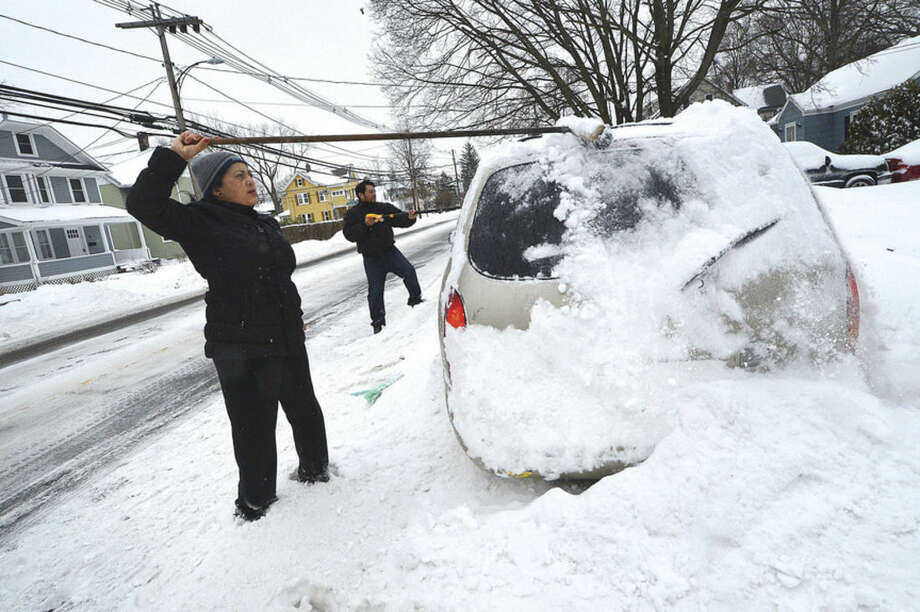 Hour Photo/Alex von Kleydorff Amalia Bonilla and Oscar Lopez use brooms and shovels to dig out their car during Monday's winter storm