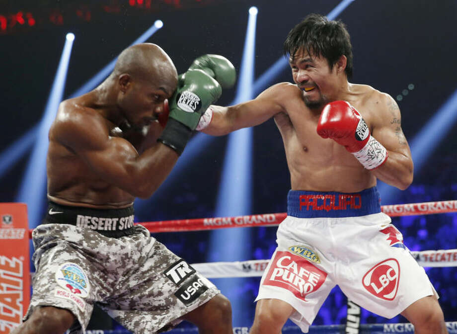 Manny Pacquiao, right, of the Philippines, throws a right at the head of Timothy Bradley during the WBO welterweight title boxing fight Saturday, April 12, 2014, in Las Vegas. (AP Photo/Eric Jamison)