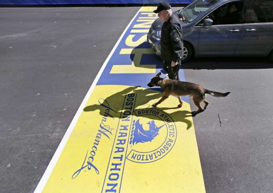 Boston Police officer John Quinn walks with, Miller, his bomb detection canine, over the finish line while sweeping the area in preparation for the Boston Marathon, Wednesday, April 16, 2014, in Boston. (AP Photo/Charles Krupa)