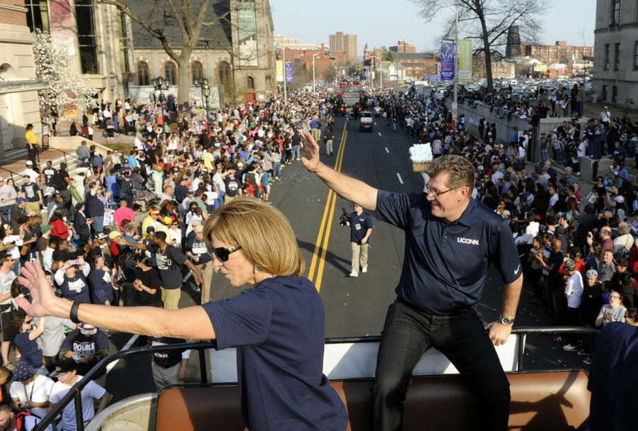 Connecticut women's coach Geno Auriemma, right, and associate head coach Chris Daily wave to a crowd during a parade in Hartford, Conn., on Sunday, April 13, 2014, celebrating the team's NCAA championship. (AP Photo/Fred Beckham)