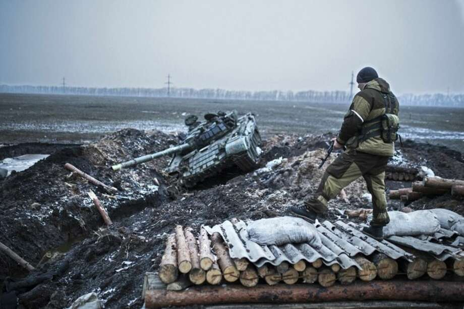A pro-Russian rebel guards a captured former Ukrainian Army checkpoint outside Vuhlehirsk, Donetsk region, eastern Ukraine, Thursday, Feb. 5, 2015. The rebels have closed in around the town in a strategy they triumphantly refer to as the Debaltseve cauldron. Separatists recently burst through government lines in the rural settlement of Vuhlehirsk. (AP Photo/Vadim Braydov)