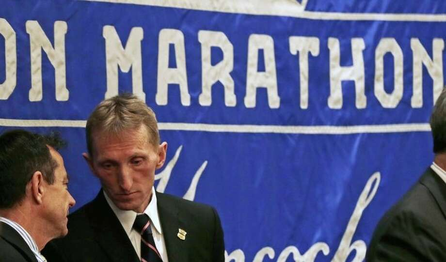 Boston Police Commissioner William Evans, second from left, listens to Boston Marathon Race Director Dave McGillivray during a news conference in preparation for the Boston Marathon, Wednesday, April 16, 2014, in Boston. (AP Photo/Charles Krupa)