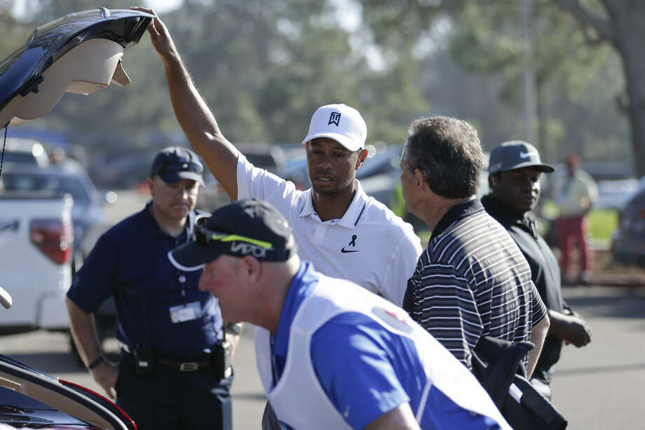 Tiger Woods loads his car after withdrawing in the first round of the Farmers Insurance Open golf tournament Thursday, Feb. 5, 2015, in San Diego. (AP Photo/Gregory Bull)