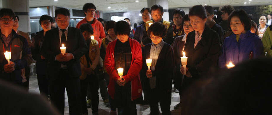Parents attend a candle light vigil to hope for their children's safe return at Danwon high school in Ansan, South Korea, Wednesday, April 16, 2014. A South Korean passenger ship carrying more than 470 people, including many high school students, sunk off the country's southern coast Wednesday after sending a distress call, officials said. (AP Photo/Yonhap) KOREA OUT