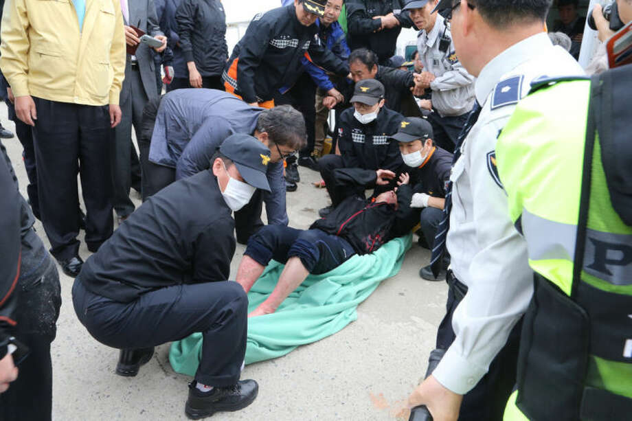 A rescued passenger from a ferry sinking off South Korea's southern coast, is carried by police and rescue teams on his arrival at Jindo port in Jindo, south of Seoul, South Korea, Wednesday, April 16, 2014. Dozens of rescue boats and helicopters are scrambling to save more than 470 people, including many high school students, caught on a ferry sinking off South Korea's southern coast, officials said. There are no immediate reports of causalities. (AP Photo/Park Chul-heung, Yonhap) KOREA OUT