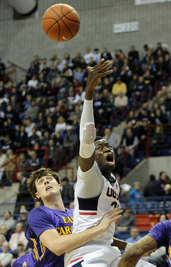 Connecticut's Amida Brimah, right, fights for a rebound with East Carolina's Marshall Guilmette (41) during the first half of an NCAA college basketball game in Storrs, Conn., on Wednesday, Feb. 4, 2015. (AP Photo/Fred Beckham)