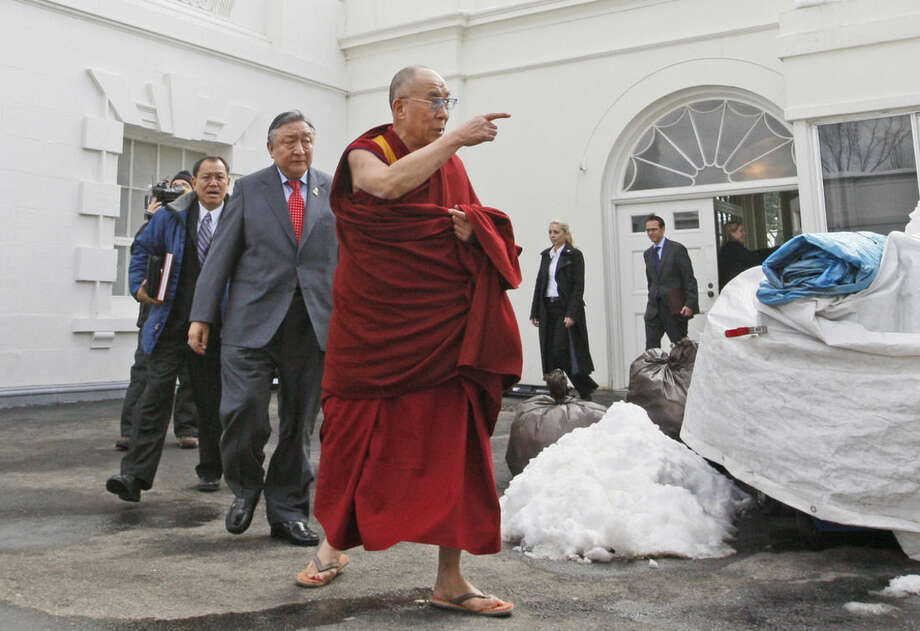 FILE - The Dalai Lama walks out of the White House in Washington, in this Thursday, Feb. 18, 2010 file photo, after meeting with President Barack Obama. Obama is to sit at the head table Thursday Feb. 5, 2015 with other speakers for the annual National Prayer Breakfast, which brings together U.S. and international leaders from different parties and faiths for one spiritual hour. Event organizers say the spiritual leader of Tibetan Buddhism will be in the audience of about 3,600, seated close to the dais and actor Richard Gere, a friend and follower. (AP Photo/Charles Dharapak, File)