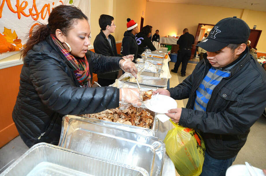 Hour Photo/Alex von Kleydorff Barbara Vazquez serves some fresh turkey during Thanksgiving dinner at NEON. Along with the turkey, guests had a choice of Macaroni and cheese, collard greens , rice, gravy, mashed potatoes and dessert. more that 30 turkeys were served