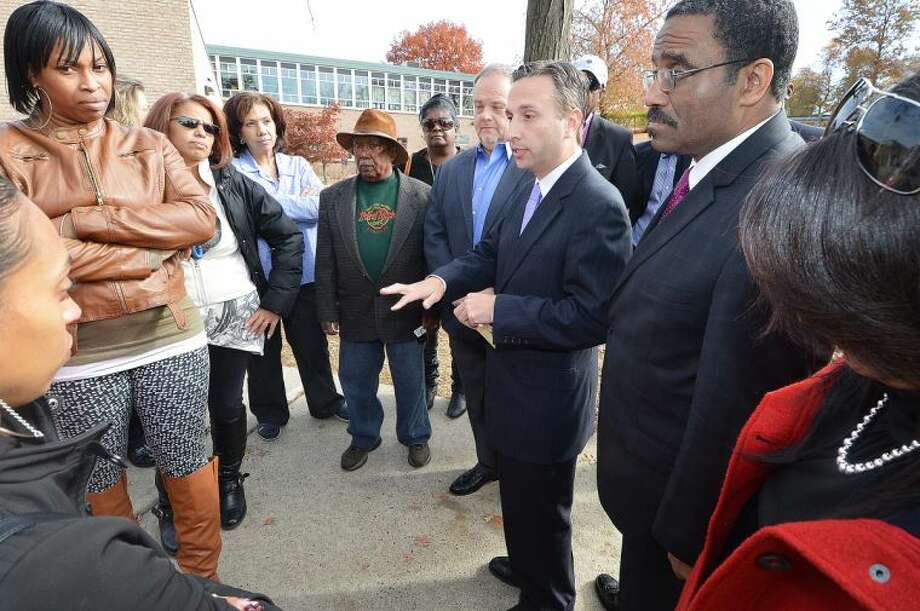 Hour Photo/Alex von Kleydorff . Michael Berkoff, CEO of NEON/ CTE, State Sen. Bob Duff and Rep. Bruce Morris speak to parents outside Nathaniel Ely school about the troubled NEON orginization
