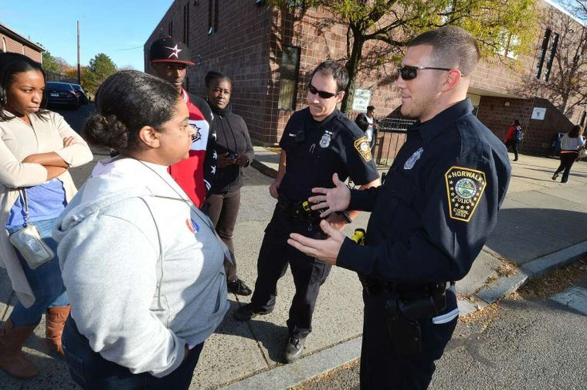 """Hour Photo/Alex von Kleydorff NEON employees speak with officers of the Norwalk Police Department who were relaying information from NEON officials about why late paychecks were bouncing. Acting CEO/President Chiquita Stephenson was """"not in the building,"""" people were told."""