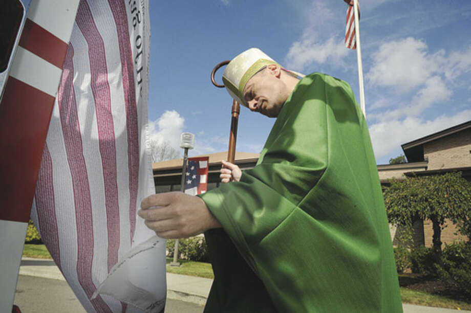 Hour photo/Matthew VinciBishop Frank J. Caggiano looks at the Flag of Heroes Sunday on Norwalk Fire Truck Number 1 in front of St. Matthew Church during the annual Diocesan Blue Mass in honor of police, fire and rescue workers.