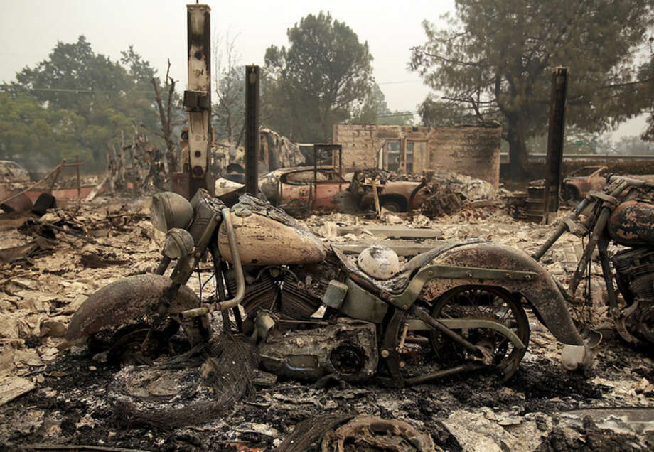 A motorcycle sits among burnt remains from a wildfire in Middletown, Calif., Sunday Sept. 13, 2015. Two of California's fastest-burning wildfires in decades overtook several Northern California towns, destroying homes and sending residents fleeing. (Kent Porter/The Press Democrat via AP) MANDATORY CREDIT