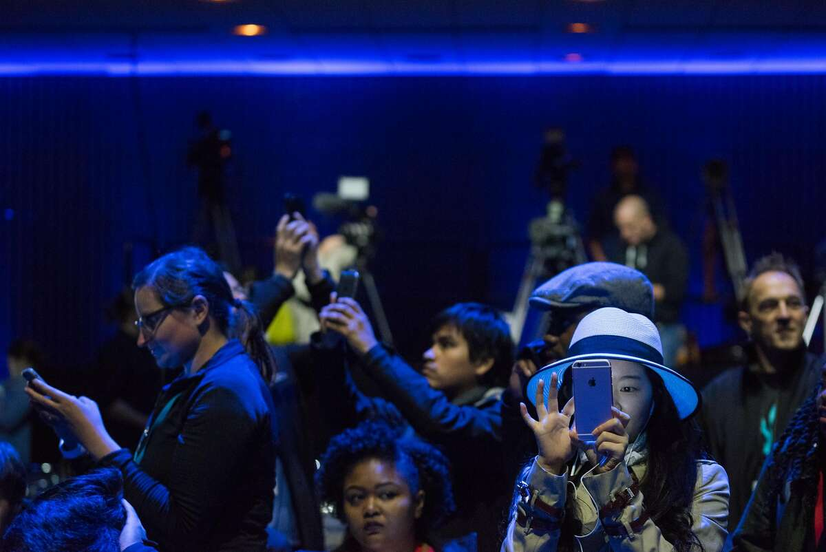 A woman uses her phone before the Apple World Wide Developers Conference at the Bill Graham Civic Auditorium in San Francisco, Calif. on Monday, June 13, 2016.