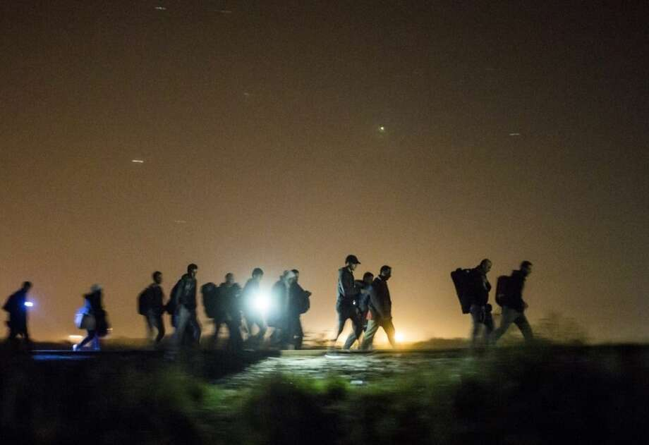 In this Sunday Sept. 13, 2015 photo migrants walk towards a checkpoint along the railway tracks connecting Horgos and Szeged near Roszke, in the vicinity of the border between Hungary and Serbia. (Balazs Mohai/MTI via AP)