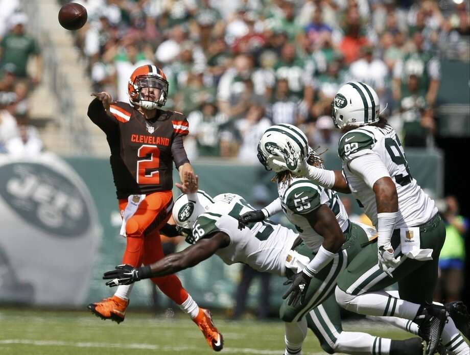 Cleveland Browns quarterback Johnny Manziel (2) throws a pass while evading New York Jets inside linebacker Demario Davis (56), Lorenzo Mauldin (55) and Kevin Vickerson (92) during the first half of an NFL football game Sunday, Sept. 13, 2015 in East Rutherford, N.J. (AP Photo/Kathy Willens)
