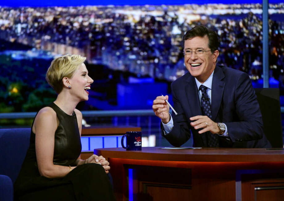 """In this image released by CBS, host Stephen Colbert, right, laughs with Scarlett Johansson during a taping of """"The Late Show with Stephen Colbert,"""" Wednesday, Sept. 9, 2015 in New York. Johansson was Colbert's guest, the second straight night he featured a celebrity who also played a prominent role in predecessor David Letterman's final run of shows. (Jeffrey R. Staab/CBS via AP)"""