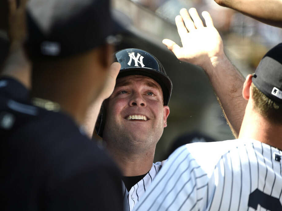 New York Yankees' Brian McCann celebrates with teammates in the dugout after scoring on Dustin Ackley's sacrifice fly in the second inning of a baseball game against the Toronto Blue Jays at Yankee Stadium, Sunday, Sept. 13, 2015, in New York. (AP Photo/Kathy Kmonicek)