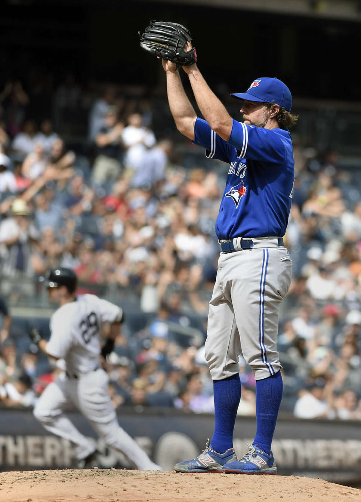 Toronto Blue Jays starting pitcher R.A. Dickey, right, reacts on the mound as New York Yankees' Dustin Ackley rounds third base after hitting a two-run home run in the fourth inning of a baseball game at Yankee Stadium, Sunday, Sept. 13, 2015, in New York. (AP Photo/Kathy Kmonicek)