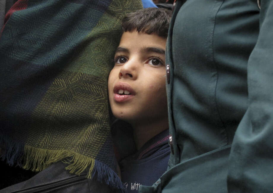 """Laith Egbari, 7 years old from Aleppo, Syria, waits in line to board a train at Keleti train station in Budapest, Hungary, Thursday, Sept. 10, 2015. Earlier, Austria's rail company announced the surprise cancellation of all of its cross-border services with Hungary, citing what it called """"a massive overload"""" of its services. That caused tensions to build at Budapest's central Keleti station, where dozens of daily services were scheduled to reach the Austrian capital, Vienna. Several hundred people from the Middle East, Asia and Africa were kept waiting for up to 10 hours with tickets in hand as police penned them into one section of the entrance. (AP Photo/Shawn Pogatchnik)"""
