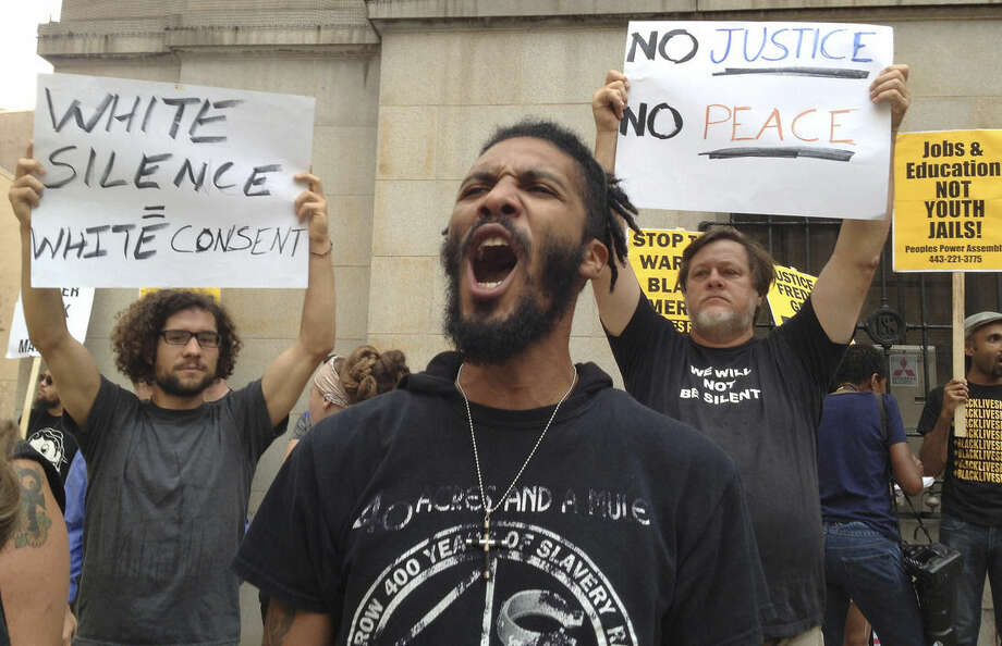 "Protesters gather outside Baltimore Circuit Court, as the first court hearing was set to begin in the case of six police officers criminally charged in the death of Freddie Gray, on Wednesday, Sept. 2, 2015 in Baltimore. Six police officers face charges that range from second-degree assault, a misdemeanor, to second-degree ""depraved-heart"" murder. (Lloyd Fox/The Baltimore Sun via AP) WASHINGTON EXAMINER OUT; MANDATORY CREDIT"