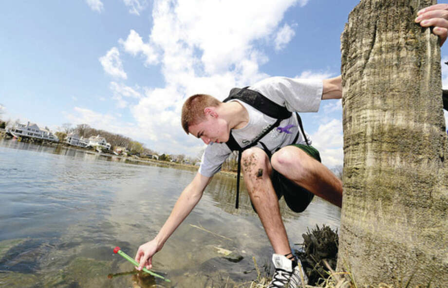Hour photo / Erik Trautmann Junior Ryan Dudek measures water temperature as 80 Norwalk High School chemistry students tour the Shoendorf, Farm Creek preserve estuary while they perform enviromental testing Friday morning.