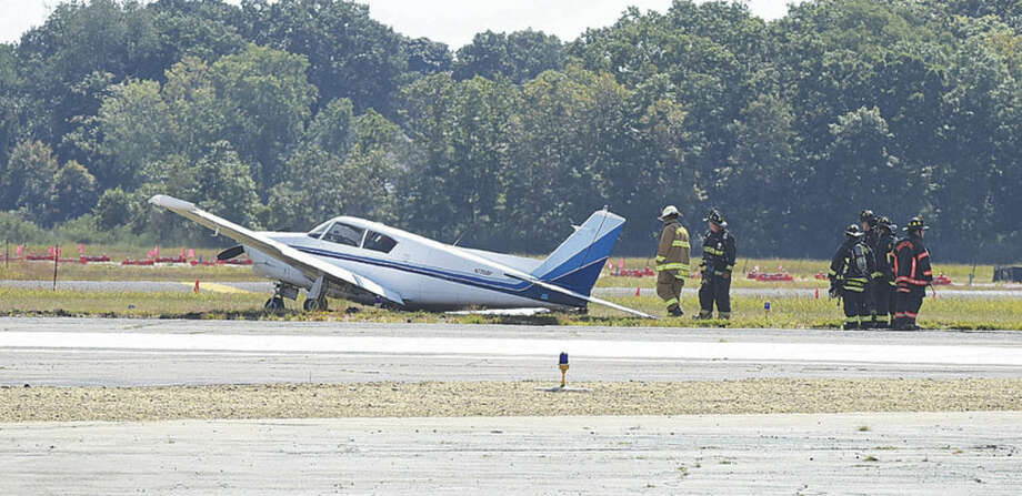 Hour photo/John Nash - Bridgeport and Stratford firefighters overlook a small plane that crashed on take off from Sikorsky Airport in Stratford on Monday afternoon. According to witnesses, the pilot appeared to abort the take off and skidded off the runway, tilting to one side.