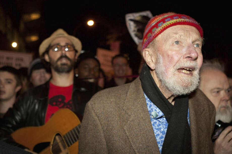 FILE- In this Oct. 21, 2011, file photo activist musician Pete Seeger, 92, right, marches with nearly a thousand demonstrators sympathetic to the Occupy Wall Street protests to hold a brief acoustic concert in New York's Columbus Circle. The singer and activist, who revered the masses and declined any personal honors in life, will be celebrated with a few early events planned on what would have been his 95th birthday, Saturday, May 3, 2014. (AP Photo/John Minchillo, File)