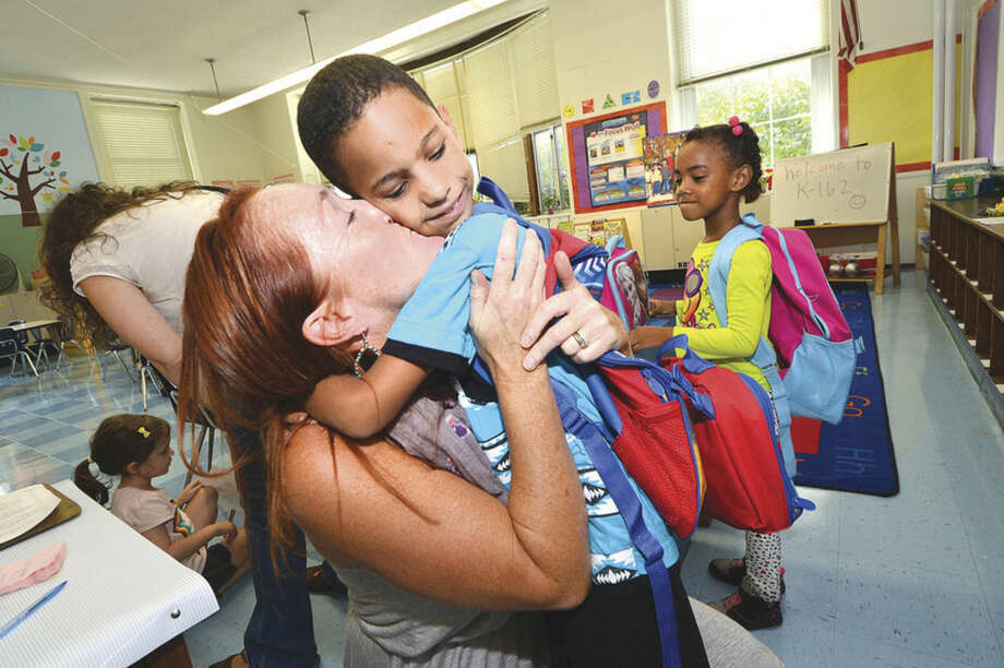 Hour Photo/Alex von Kleydorff Willi Angel is off to his first grade class but not before he says hello and gets a hug and a kiss from his Kindergarten Teacher from last year, Katie Restrepo at Columbus Magnet School on the first day back for Norwalk schools