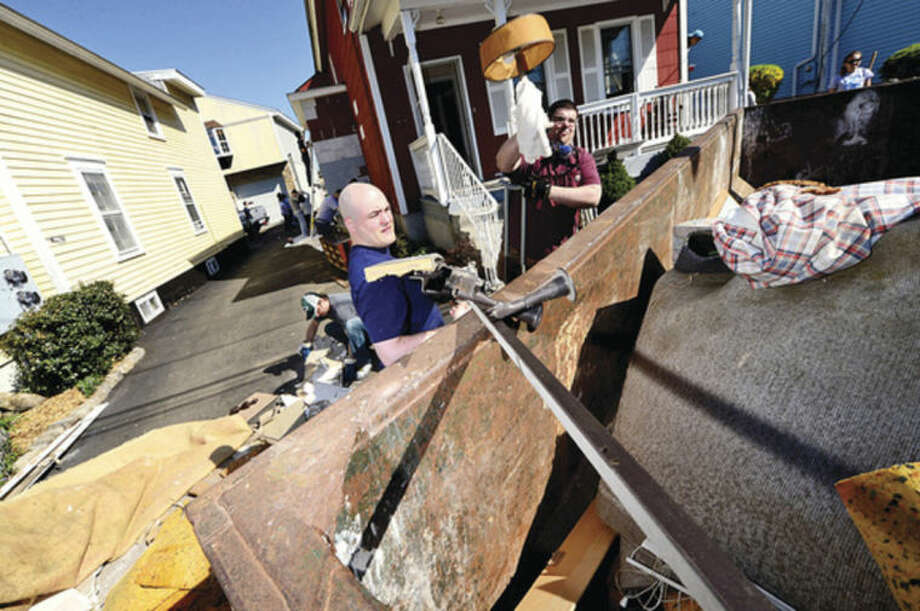 Hour photo / Erik Trautmann Facset Volunteers repair a house at 9 Moore Place in Norwalk for HomeFront Day Saturday.