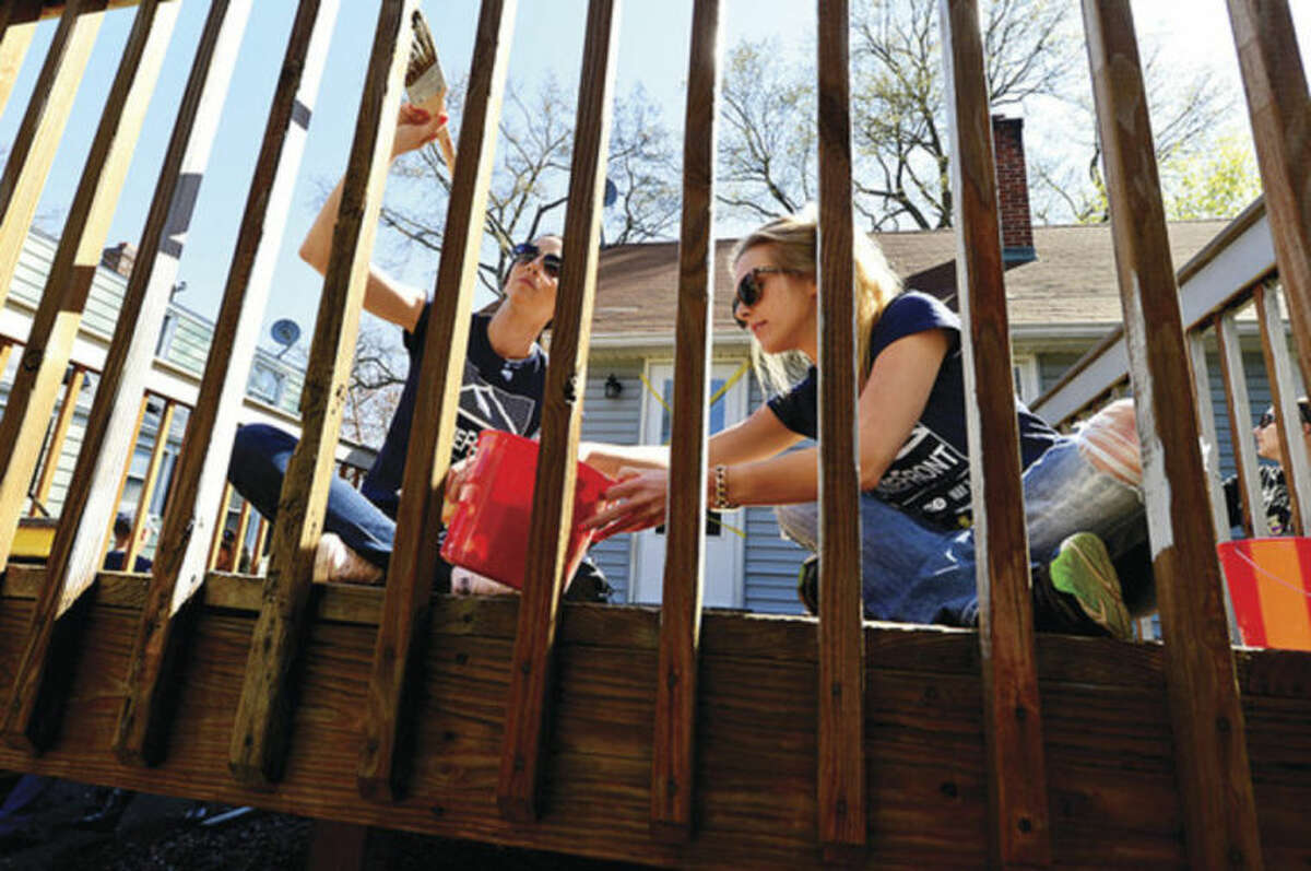 Hour photo / Erik Trautmann This Old House volunteer Kayla Gambino and Kelly large paint a deck at a home on Walter Ave in Norwalk for HomeFront Day Saturday.