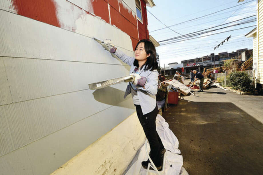 Hour photo / Erik Trautmann Facset Volunteer XiXu Cai paints the exterior of a house at 9 Moore Place in Norwalk for HomeFront Day Saturday.