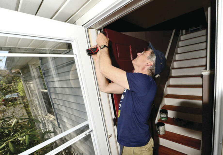 Hour photo / Erik Trautmann This Old House volunteer Tom Baker fixes a doorway at a home on Walter Ave in Norwalk for HomeFront Day Saturday.