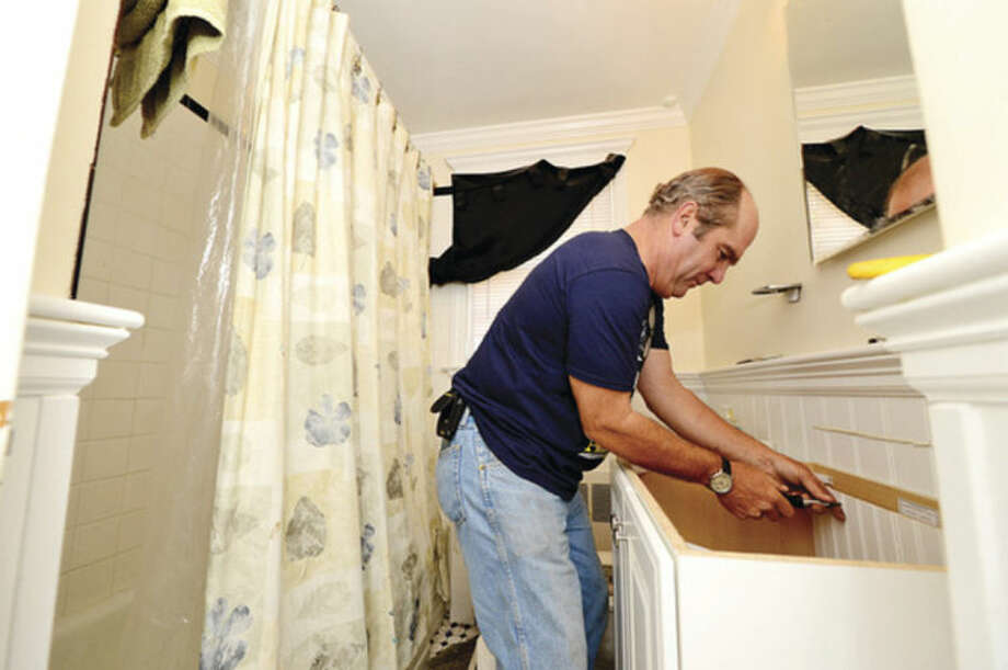 Hour photo / Erik Trautmann This Old House volunteer Richard Trethewey replaces a vanity at a home on Walter Ave in Norwalk for HomeFront Day Saturday.