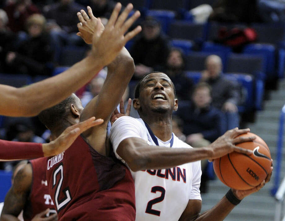 Connecticut's DeAndre Daniels, right, drives past Temple's Will Cummings (2) during the first half of an NCAA college basketball game in Hartford, Conn., Tuesday. Jan. 21, 2014. (AP Photo/Fred Beckham)