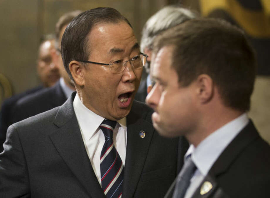 United Nations Secretary-General Ban Ki-moon, left, reacts as he arrives for the conference on Disarmament at the United Nations headquarters in Geneva, Switzerland, Tuesday, Jan. 21, 2014. Ban Ki-moon arrived to join this week's Syria peace talks in Montreux and Geneva. Russian Foreign Minister Sergey Lavrov said that Ban Ki-moon's decision to withdraw his last-minute offer to Iran to attend the conference set to begin in the Swiss resort of Montreux would have a negative impact on the United Nations image. (AP Photo/Anja Niedringhaus)