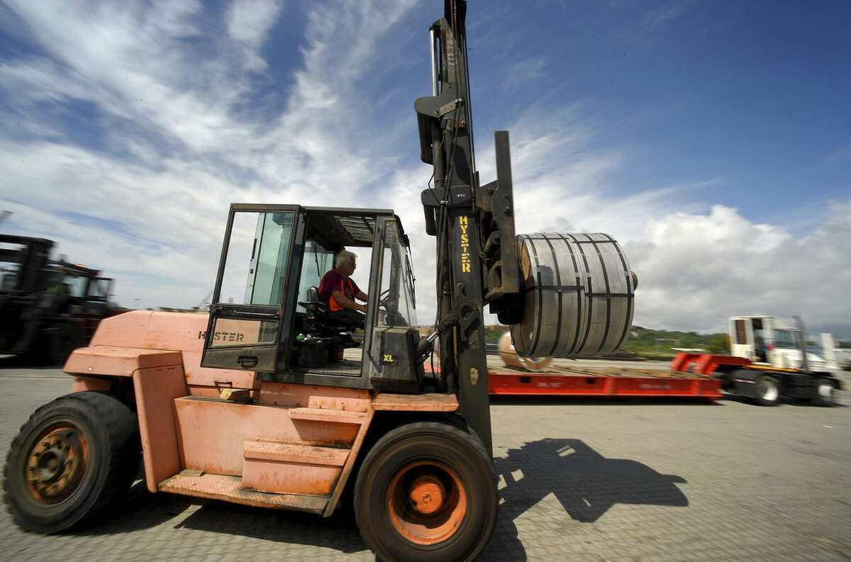 In this July 14, 2015 photo, a coil of steel is carried by forklift to the warehouse after it was unloaded from a cargo ship by workers at the Logistec USA terminal at the Adm. Harold E. Shear State Pier in New London, Conn. The stevedores spent two full days unloading steel products for distribution throughout New England. (Tim Cook/The Day via AP) MANDATORY CREDIT