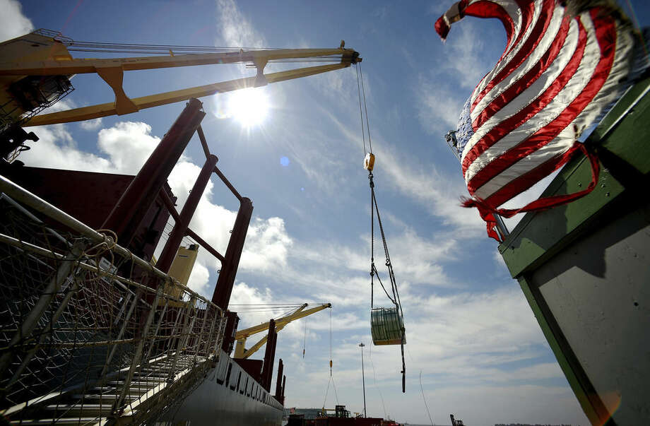 In this July 14, 2015 photo, multiple-ton coils of steel are unloaded from the cargo ship Selinda by workers at the Logistec USA terminal at the Adm. Harold E. Shear State Pier in New London, Conn. About two dozen cargo vessels arrive each year in New London, most carrying steel from Belgium and Germany. (Tim Cook/The Day via AP) MANDATORY CREDIT