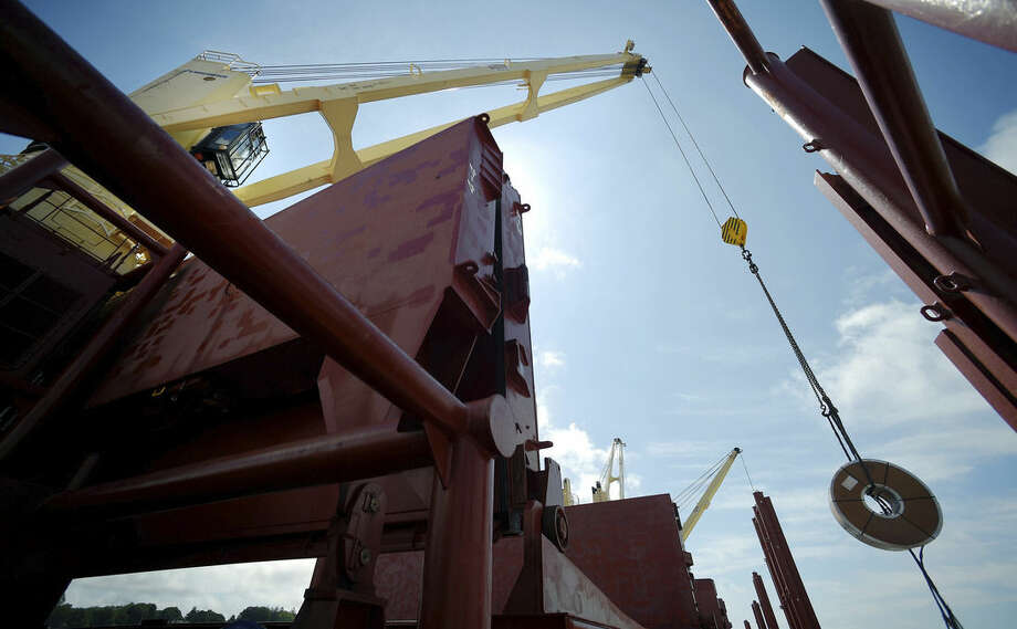 In this July 14, 2015 photo, multiple-ton coils of steel are unloaded from the cargo ship Selinda by workers at the Logistec USA terminal at the Adm. Harold E. Shear State Pier in New London, Conn. The Selinda transported 5,500 metric tons of manufactured steel from Antwerp, Belgium. (Tim Cook/The Day via AP) MANDATORY CREDIT