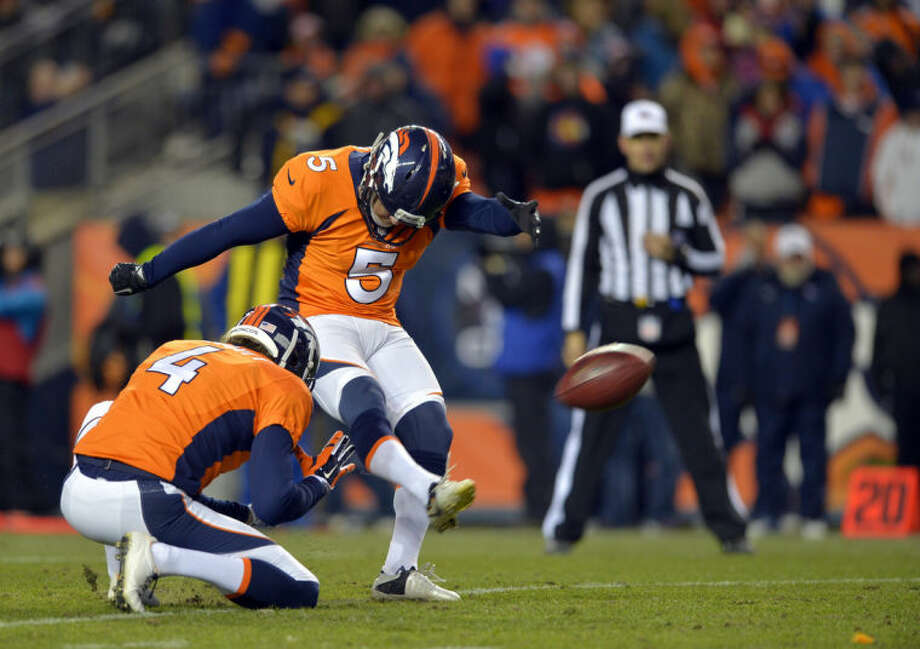 FILE - In this Jan. 12, 2014, file photo, Denver Broncos kicker Matt Prater (5) kicks an extra point as Broncos punter Britton Colquitt (4) holds during the fourth quarter of an AFC divisional playoff NFL football game against the San Diego Chargers in Denver. NFL Commissions Roger Goodell doesn't want to stand pat with the PAT. He's suggesting potential changes in the extra point that, well, might have some legs.(AP Photo/Jack Dempsey, File)