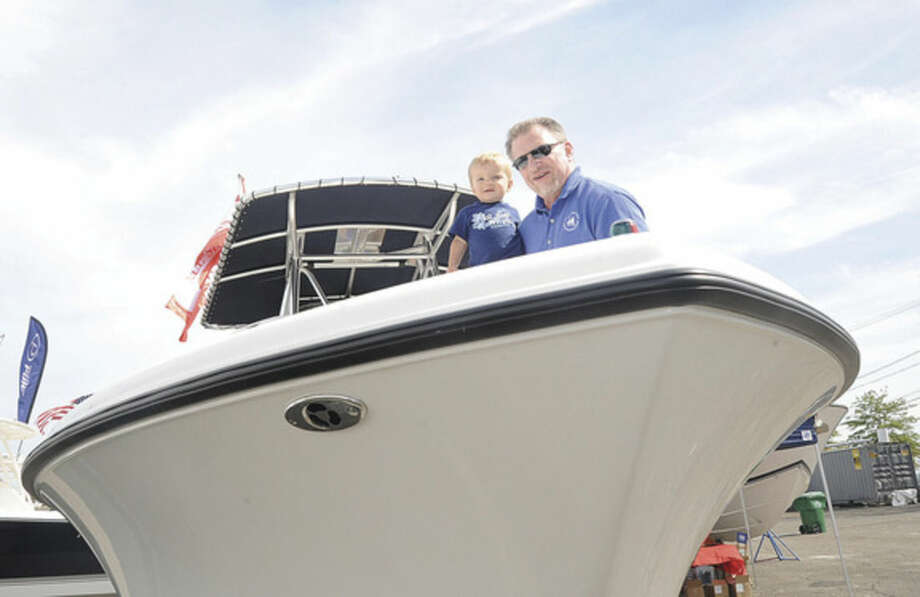 Steve Carroll shows 1 year old Joseph Bradford around 23 ft. Pursuit Saturday at the Norwalk Boat Show. Hour photo/Matthew Vinci