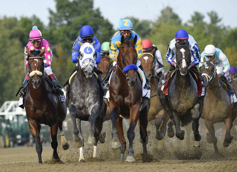 """FILE - In this Aug. 29, 2015, file photo, Triple Crown winner American Pharoah, center, with jockey Victor Espinozaup, leads the field into the first turn during the Travers Stakes horse race at Saratoga Race Course in Saratoga Springs, N.Y. The owner of American Pharoah says the Triple Crown winner will run again before he is retired at the end of the year. Ahmed Zayat tweeted Thursday, Sept. 3, 2015, he has """"decided to continue to race American Pharoah! The champ deserves another chance!"""" (AP Photo/Hans Pennink, File)"""