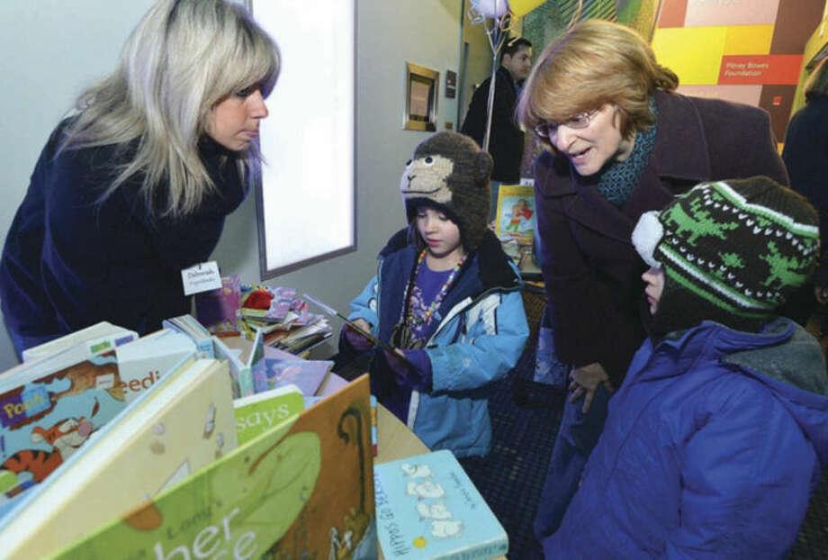 Hour Photo/Alex von Kleydorff.Deborah Przewlocki helps twins Lydia and Baxter Colbath decide on a book about owls with their mom Julie at Stepping Stones Musem