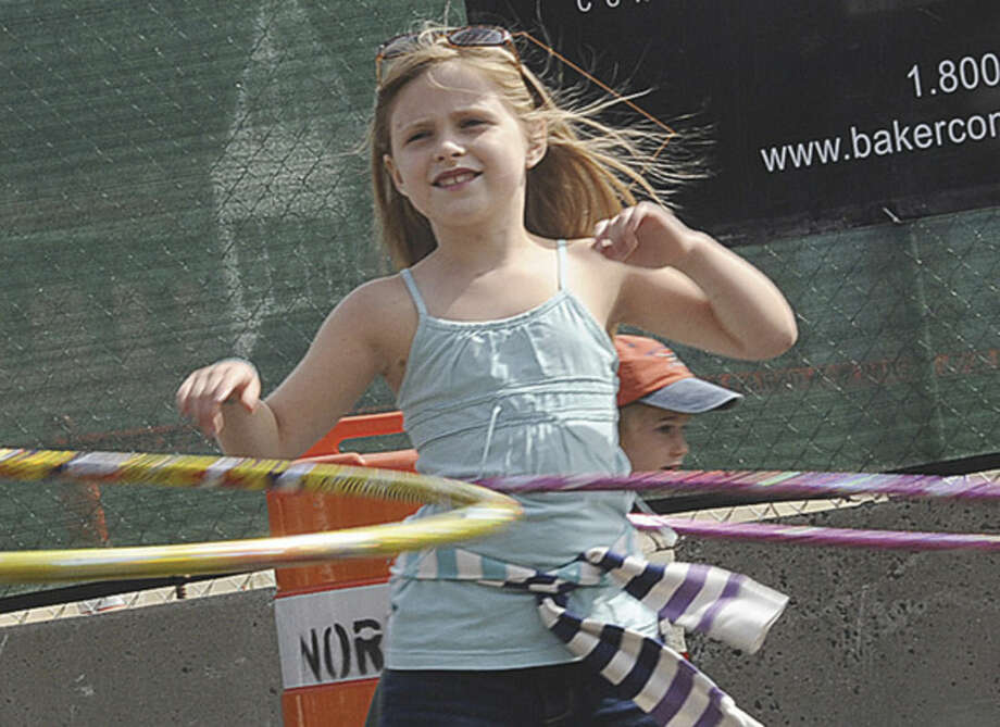 Emily Anderson 7, enjoys the street festival celebrating the 100th anniversary of the Wall Street Theater on Sunday. Hour photo/Matthew Vinci