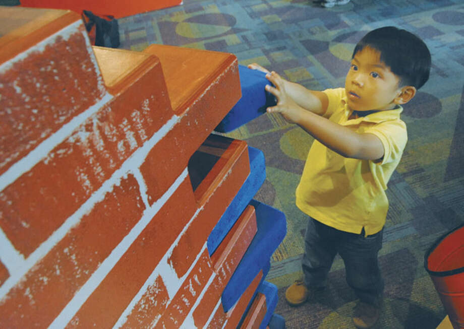 Three year old Baron Uy rebuilds a brick wall Saturday at the Stepping Stones Museum for Children at the opening ofn the new exhibit Broken? Fix it. Hour photo/Matthew Vinci