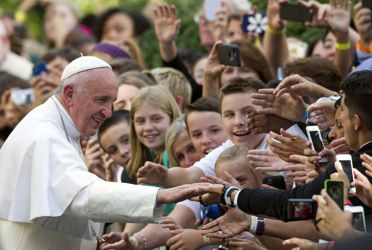 Pope Francis shakes hands with school children as he departs the Apostolic Nunciature, the Vatican's diplomatic mission in the heart of Washington, en route Andrews Air Force Base, Thursday, Sept. 24, 2015. (AP Photo/Cliff Owen)